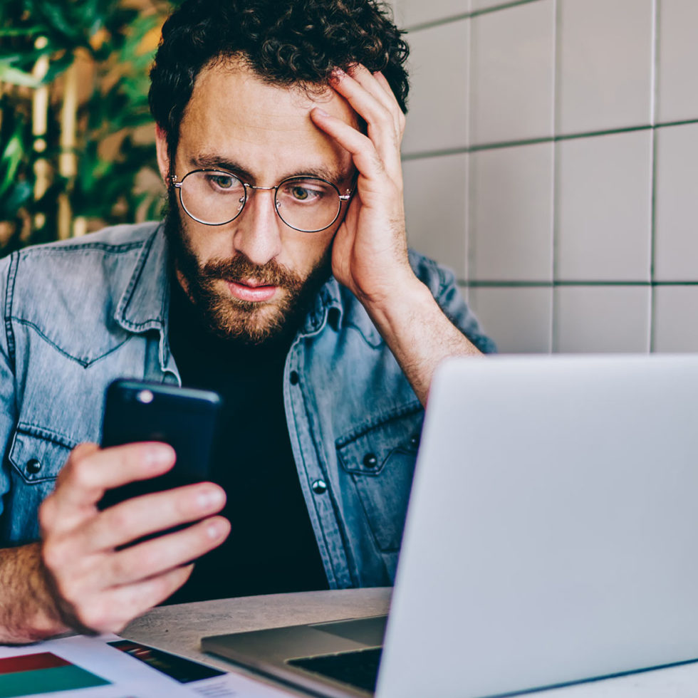 guy looking at smartphone in front of laptop